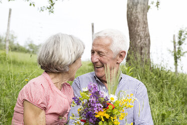 Happy senior couple with bunch of flowers outdoors - RBF004769