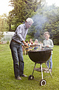 Grandfather and granddaughter on a family barbecue - RBF004772