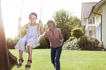Grandmother and happy granddaughter on swing in garden - RBF004796