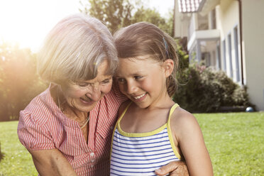 Happy grandmother and granddaughter in garden - RBF004799