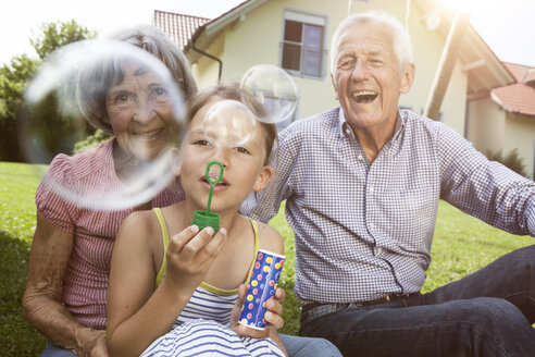 Grandparents and granddaughter in garden blowing soap bubbles - RBF004802