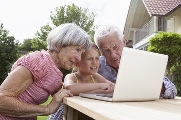 Grandparents and granddaughter using laptop in garden - RBF004808