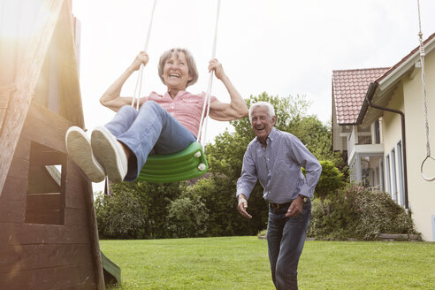 Playful senior couple with swing in garden - RBF004817