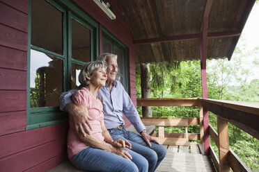 Happy senior couple relaxing on porch of log cabin - RBF004820