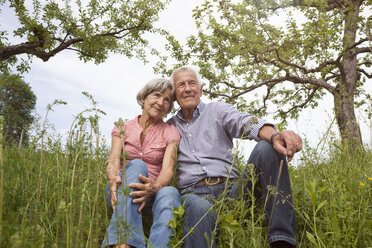 Relaxed senior couple sitting in meadow - RBF004826