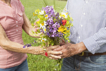 Senior couple with bunch of flowers outdoors - RBF004829