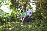 Grandfather and grandson sitting outdoors together - RBF004835