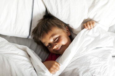 Smiling little boy lying in bed trying to sleep - VABF000714