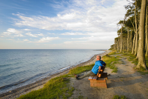 Germany, Nienhagen, Baltic Sea, Gespensterwald, beach, men sitting on bench in the morning - RJF000610