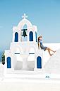 Greece, Santorini, Oia, woman sitting on spur of belltower - GEMF000929