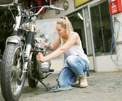 Young woman repairing motorbike - MADF001034