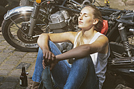 Young woman with beer bottle leaning against motorbike - MADF001046