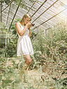 Young woman in white dress taking pictures in greenhouse - MADF001049