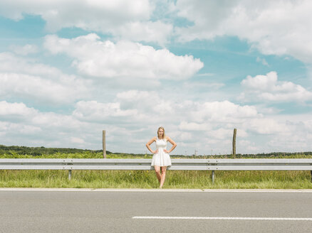 Young woman in white dress standing at the roadside - MADF001052