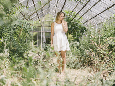 Blond young woman in white dress standing in greenhouse - MADF001058