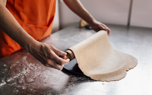 Hands of woman rolling out pizza dough, close-up - MGOF002077