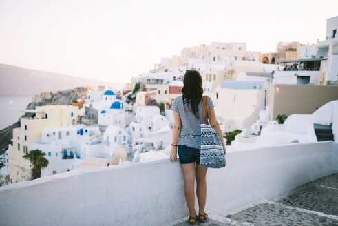Greece, Santorini, Oia, back view of  woman looking to the village at evening twilight - GEMF000937