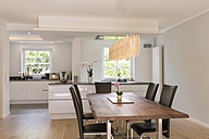 Modern dining area with open plan kitchen in the background - SHKF000632