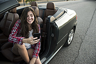 Smiling young woman sitting in convertible looking at smartphone - ABZF000882