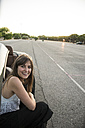 Smiling young woman crouching beside convertible - ABZF000885