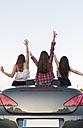 Back view of three friends standing in convertible with raised arms - ABZF000888