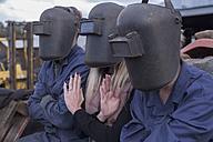 Three people wearing welding helmets outdoors - ZEF009316