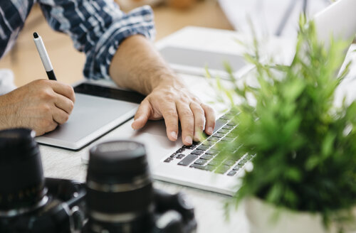 Photographer working at desk with graphics tablet, partial view - JRFF000781