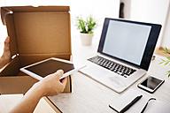Woman unpacking parcel on her desk - JRFF000790
