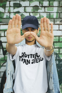 Portrait of starring young man wearing t-shirt with saying 'Hotter Than Hell' stretching out his arms - JUBF000173