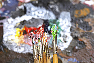 Different used paintbrushes in front of artist's palette - JTF000767