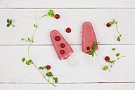 Two homemade wild strawberry ice lollies on wood - GWF004857