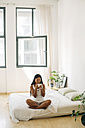 Young woman sitting on bed drinking coffee - EBSF001551