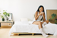 Young woman sitting on bed drinking coffee - EBSF001572