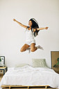 Exuberant young woman jumping on bed - EBSF001578