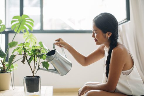Young woman at home watering plant - EBSF001599