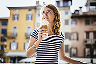Italy, Udine, portrait of smiling young woman with coffee to go - GIOF001334