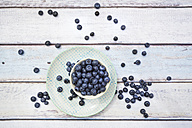Bowl and plate of blueberries on wood - LVF005186