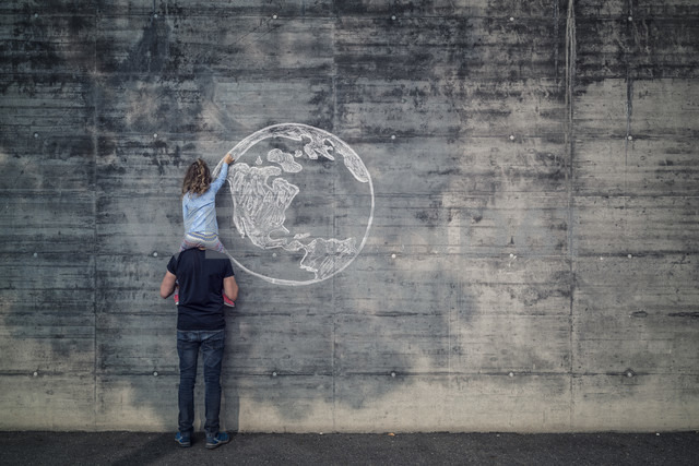 Austria, Salzburg, Father with daughter on his shoulders, the daughter draws with chalk the earth on a concrete wall - OPF000117