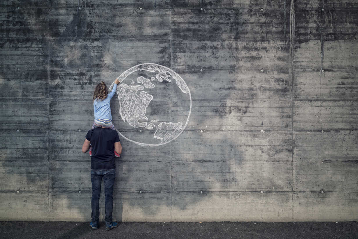 Austria, Salzburg, Father with daughter on his shoulders, the daughter draws with chalk the earth on a concrete wall - OPF000117 - Ophelia/Westend61