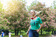 Happy blond woman with headphones walking in a park - DIGF000824