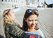 Austria, Vienna, two young women having fun in front of the parliament building - AIF000355