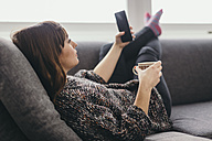 Young woman relaxing on couch with cup of coffee taking selfie with smartphone - LCUF000027