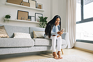 Young woman sitting on couch at home looking at smartphone - EBSF001643