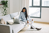 Young woman sitting on couch at home looking at laptop - EBSF001649
