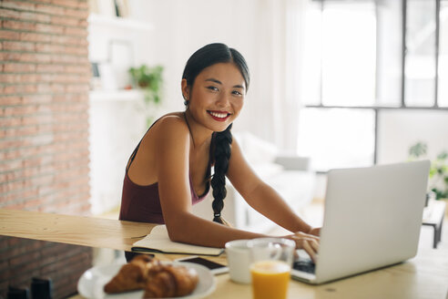 Portrait of smiling woman working with laptop at home - EBSF001665