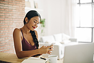 Smiling woman looking at her cell phone at home - EBSF001668