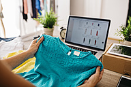 Woman holding top in front of laptop - JRFF000798
