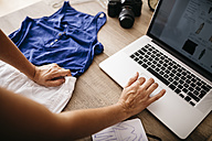 Woman with garment using laptop on desk - JRFF000807