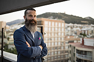 Portrait of smiling businessman with full beard standing on roof terrace looking at distance - JASF001028