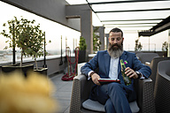 Bearded businessman sitting on roof terrace with beer bottle looking at tablet - JASF001031
